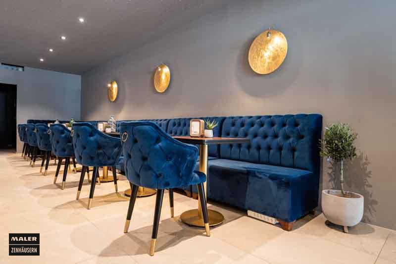 Sitzecke mit blauen Sitzpolstern und goldenen Details der Luna Cafe Bar