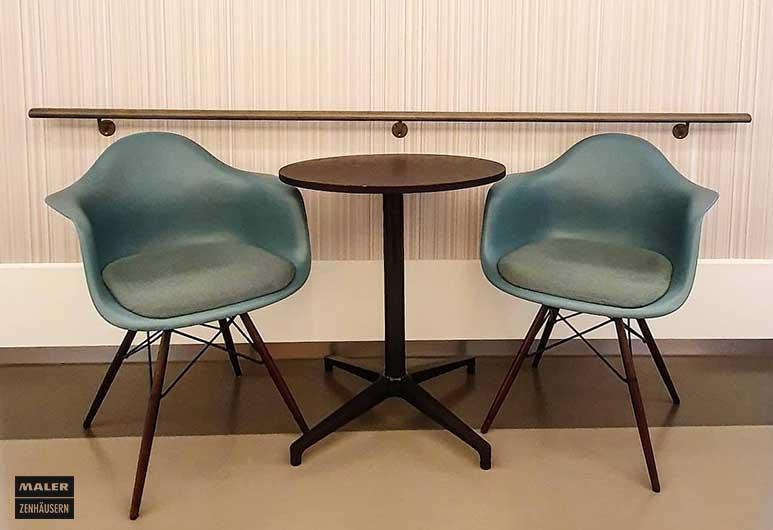 Zwei mintfarbene Vitra Stühle mit Tisch in der Mitte und Vescom Wandbekleidung