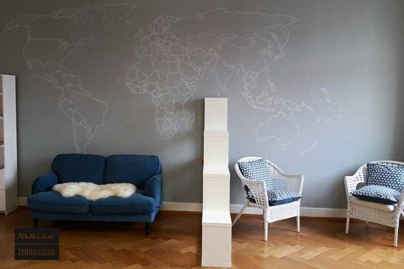 Schriftmalerei einer Weltkarte an der Wohnzimmerwand