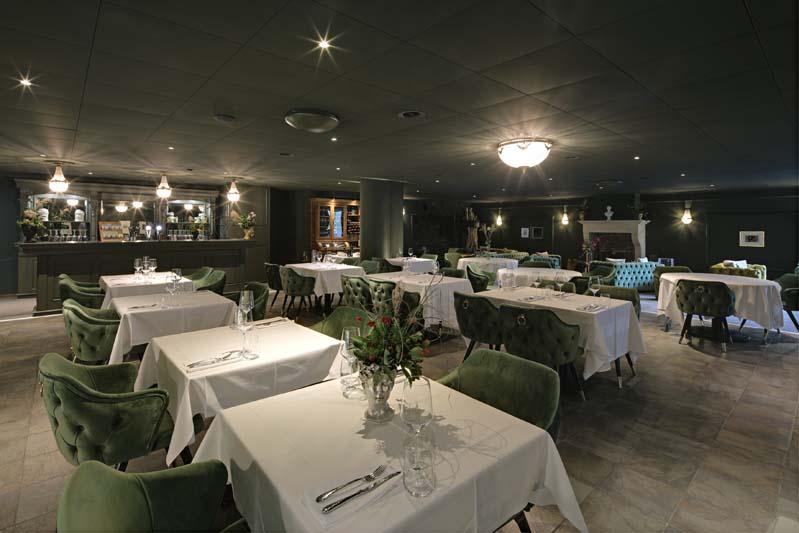 Foto eines Restaurants mit dunklen Wänden, grünen Samtsesseln und Tischen mit weissen Decken