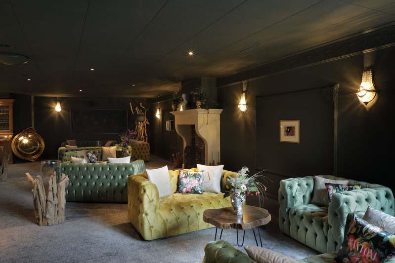 Foto eines sehr noblen Restaurants mit gemütlichen Sofas - dunkel gestrichen ist