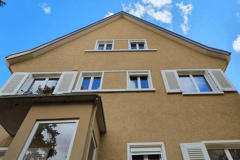 Aufnahme von unten von einem Haus. Das Haus sieht frisch saniert aus.