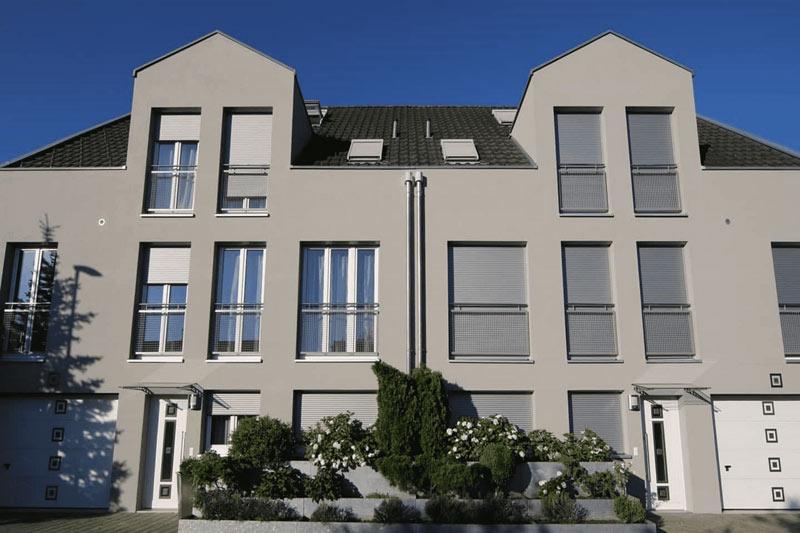Zwei moderne Doppelhaushälften in grau. Vor dem Haus grüne Anlage mit weißen Blumen und Gebüschen.