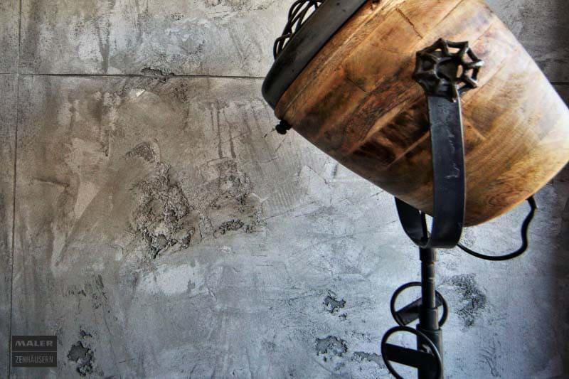 Foto einer rauen Betonwand vor der ein moderner Leuchter steht