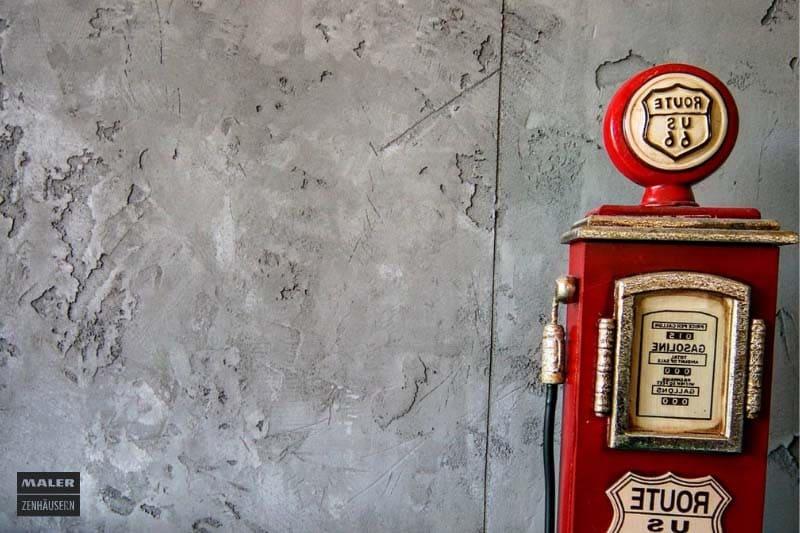 Foto einer rauen Betonwand vor der eine dekorative Zapfsäule steht
