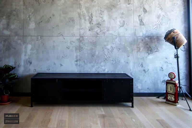 Foto einer Betonwand, vor der ein paar dekorative Objekte stehen