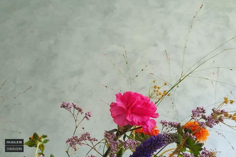 Foto eines bunten Blumenstrauss', im Hintergrund eine mint-graue Wand, die mit einer speziellen Technik veredelt wurde