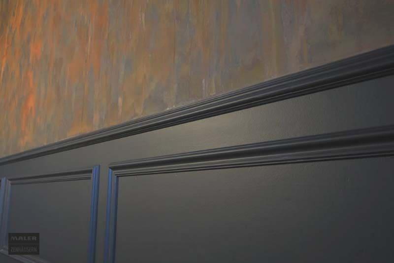 Foto einer Wand, die mit Rostoptik bearbeitet wurde und einer Leiste in dunkelgrau