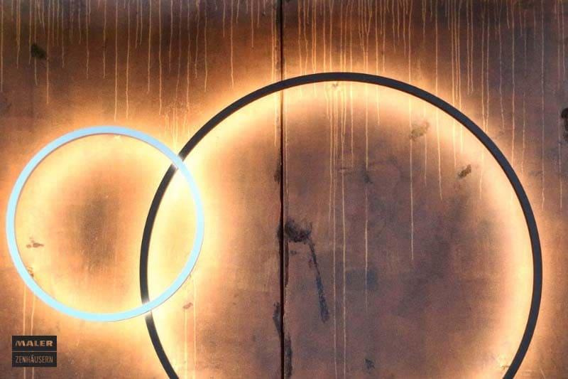 Foto einer Wand, die mit Rostoptik aufgewertet wurde. An der Wand hängen zwei runde, moderne Leuchten