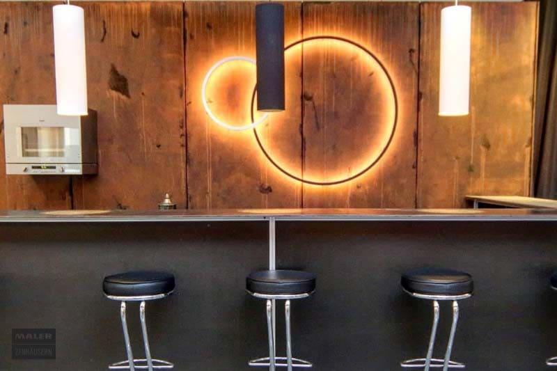 Foto einer modernen Bar mit Fokus auf die Wand im Hintergrund, die mit Rostoptik aufgewertet wurde. An der Wand hängen zwei runde, moderne Leuchten