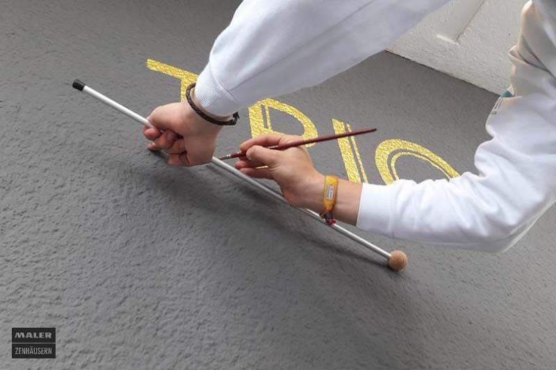 Foto einer Malerin beim Zeichnen eines feinen Logos an eine Fassade