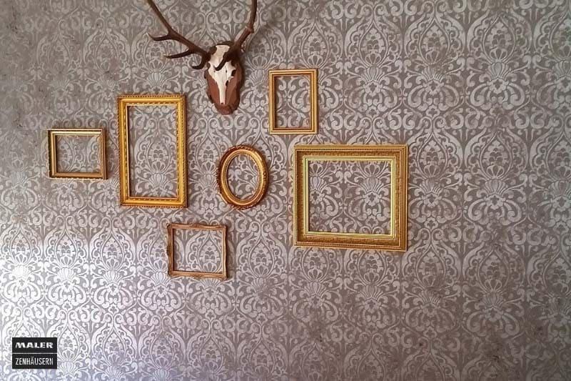 Foto einer kreativen Wandtapete mit Muster und leeren, goldenen Bilderrahmen