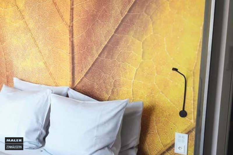 Foto eines Hotelzimmers mit Fokus auf die Wandtapete hinter dem Bett mit einem großen, goldgelben Blatt